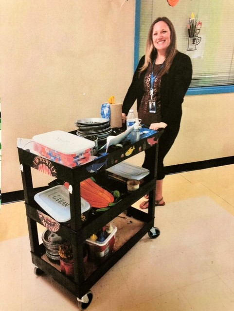 art teacher carrying supplies on a cart
