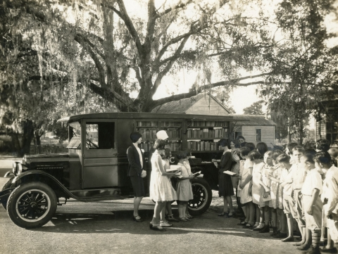 1928 book truck with a line of children eagerly waiting