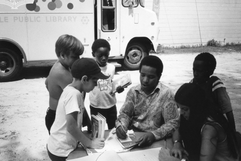 Library worker entertaining and educating children gathered beside a bookmobile