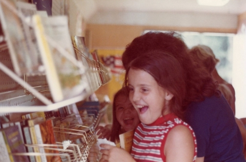 Excited child, looking at books inside a bookmobile