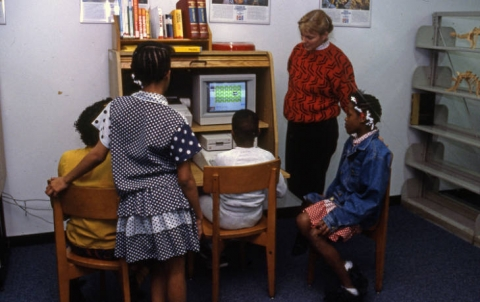 Woman and group of children using library computer