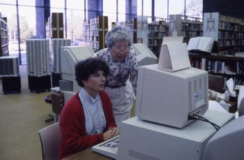 Library employee assisting customer at computer catalog