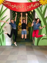 Photo of Hurley, Terri and Jenna jumping in mid air in front of the Children's Library at the Main Library