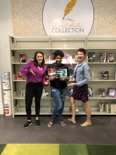 Jenna and Hurley posing with Nikesha Williams in front of the local author collection