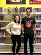 Badr Milligan of the shortbox podcast with Jenna of the Completely Booked podcast in front of the comic book collection at the Jacksonville Public Library