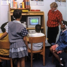 Woman and a group of children using library computer 1990s